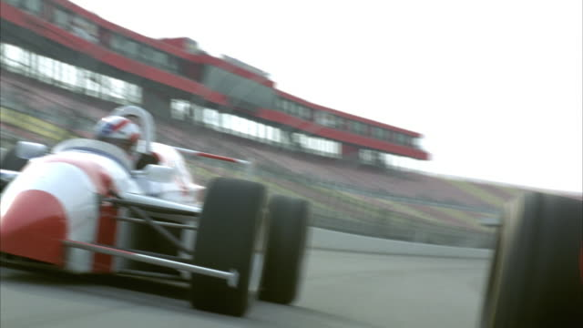 tracking shot black formula one race car with red star racing against white  formula one race car with stars and stripes pattern. pov moves from side to side as cars race counterclockwise around track. - sports track stock videos & royalty-free footage