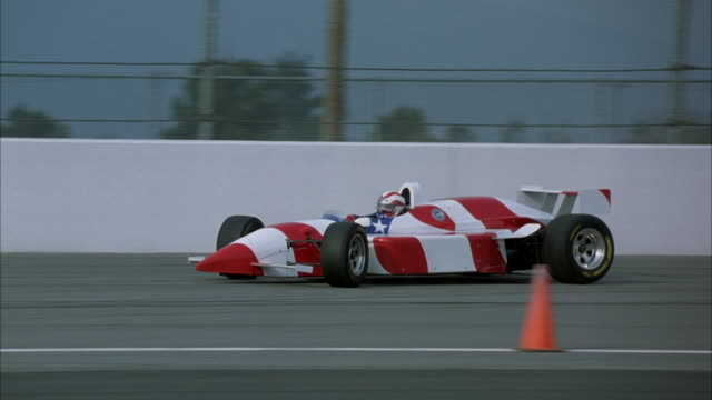 TRACKING SHOT OF FORMULA ONE RACE CAR WITH STARS AND STRIPES PATTERN AS IT ACCELERATES ALONG TRACK RIGHT TO LEFT PAST ORANGE TRAFFIC CONES.
