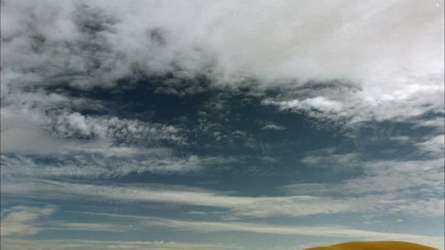 up angle of white fluffy cumulus clouds in blue sky. see top of sand dunes or dirt hills at bottom. - cumulus cloud stock videos & royalty-free footage