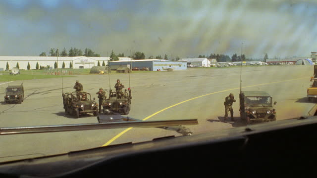 PAN LEFT TO RIGHT AS MILITARY JEEPS WITH SOLDIERS OR MARINES PULL UP IN FRONT OF THE PLANE WITH GUNS OR WEAPONS DRAWN AND AIMED AT AIRCRAFT. THIS WORKS FOR POSSIBLE HIJACKING, TERRORIST, OR HOSTAGE SITUATION (R156-2 THROUGH R158-10 MATCH)