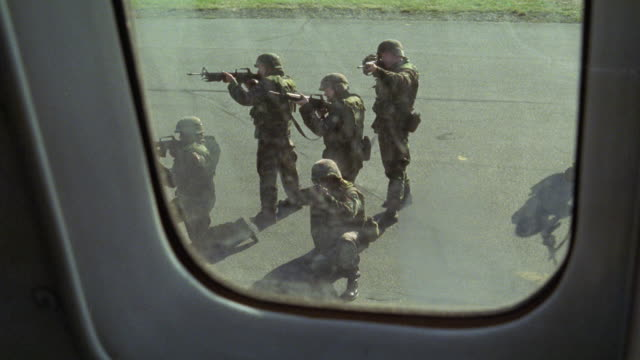 wide angle, pov from airplane passenger window to runway below as u.s. army soldiers or marines run up and aim guns or rifles at plane. - entführung ereignis mit verkehrsmittel stock-videos und b-roll-filmmaterial