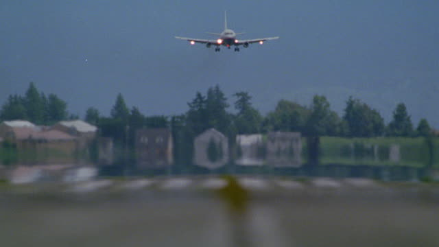 wide angle of commercial passenger jet airplane on approach for landing with landing lights on. heat from pavement. plane lands or touches down briefly and then immediately takes off again. touch and go (r156-2 through r158-10 match) - entführung ereignis mit verkehrsmittel stock-videos und b-roll-filmmaterial