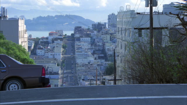 PAN LEFT TO RIGHT ON SAN FRANCISCO CITY STREET AS SEDAN CAR DRIVES UP HILL. CAMERA PANS TO FOLLOW. SAN FRANCISCO BAY IN BG. APARTMENT BUILDINGS IN BG. RESIDENTIAL AREA. CARS PARKED ON CURB.