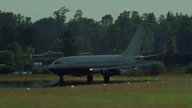 stockvideo's en b-roll-footage met pan right to left, tracking shot of commercial jet airplane (boeing 737) as it taxies on runway preparing for takes-off. plane has no markings, could be used for cargo plane. - opeenvolgende serie