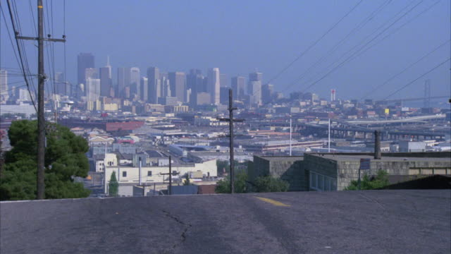 medium angle as brown cadillac speeds up san francisco hill  two police cars flash by camera. police chases or car chases. san francisco skyline and bridge in bg. - 1985年点の映像素材/bロール