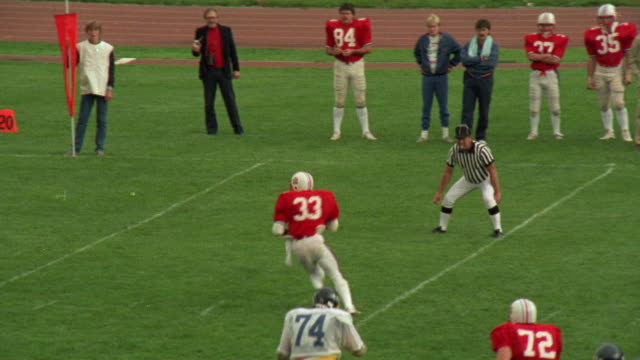 MEDIUM ANGLE OF PASSING PLAY DURING HIGH SCHOOL FOOTBALL GAME. SEE TEAM ON OFFENSE DRESSED IN RED AND WHITE UNIFORMS.