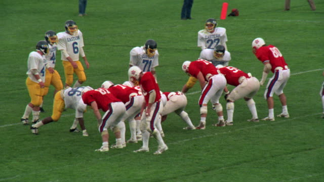 MEDIUM ANGLE OF POINT AFTER ATTEMPT DURING HIGH SCHOOL FOOTBALL GAME. SEE TEAM ON OFFENSE DRESSED IN RED AND WHITE UNIFORMS.