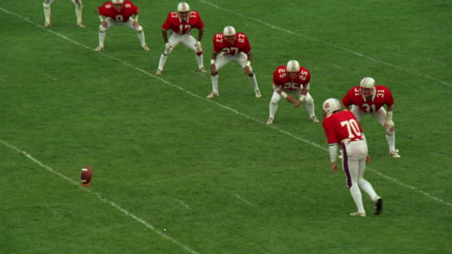 MEDIUM ANGLE OF KICK-OFF DURING HIGH SCHOOL FOOTBALL GAME. SEE TEAM ON OFFENSE DRESSED IN RED AND WHITE UNIFORMS. SEE DEFENSIVE TEAM IN YELLOW AND BLUE UNIFORMS.
