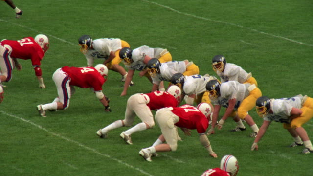 vídeos de stock, filmes e b-roll de medium angle of passing play during high school football game. see team on defense dressed in red and white uniforms. see offensive team in yellow and blue uniforms. see teams line up and quarterback throw incomplete pass about 10 yards into sideline. - bola