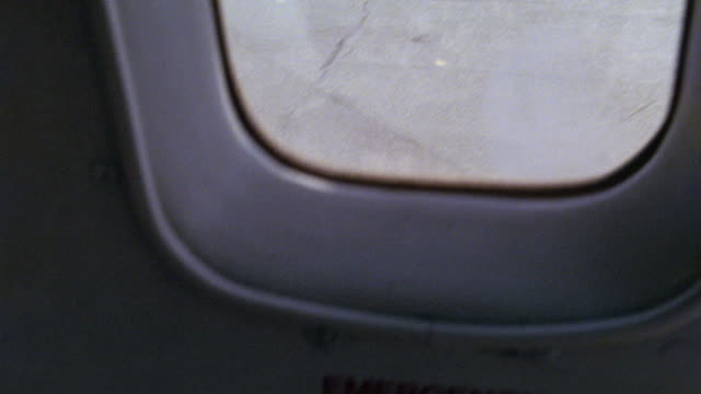 MEDIUM ANGLE POV FROM INSIDE OF AIRPLANE COMMERCIAL PASSENGER JET WINDOW FROM LEFT SIDE OF PLANE TO GROUND BELOW. PLANE IS STATIONARY.
