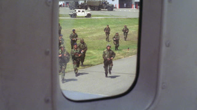 medium angle pov from airplane passenger window, left side, to ground below.  plane is on the ground and stationary. see army soldiers or marines run up and aim guns or weapons at airplane. - us military stock videos & royalty-free footage
