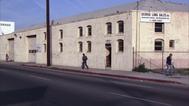 """ZOOM IN ON TWO STORY RUNDOWN WAREHOUSE """"GEORGE LONG SALES, INC. COULD BE ABANDONED. LOWER CLASS URBAN AREA. PEDESTRIANS WALK ON SIDEWALK AS CARS DRIVE DOWN STREET."""
