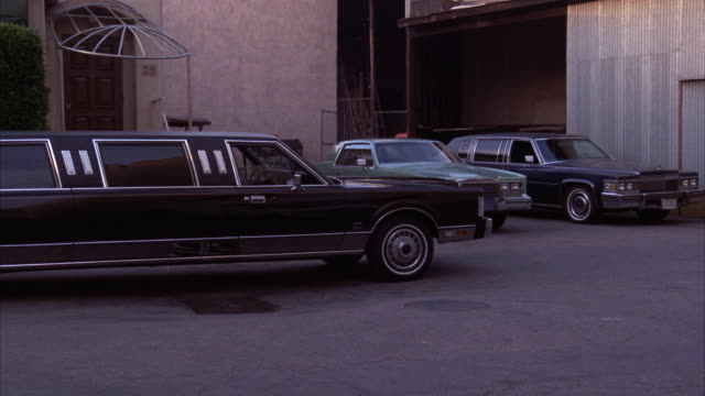 medium angle of back of warehouse area or loading dock with black stretch limousines parked. - limousine stock videos & royalty-free footage
