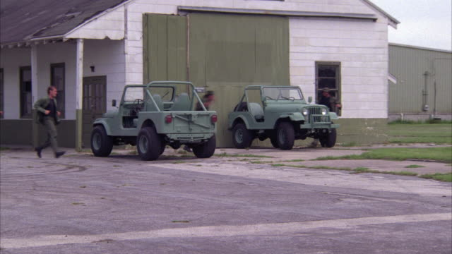 WIDE ANGLE OF MILITARY OR ARMY BASE. TWO JEEPS PARKED OUTSIDE BARRACKS, BUILDING. SOLDIERS RUN OUTSIDE AND JUMP INTO JEEPS. MEN DRIVE OFF.