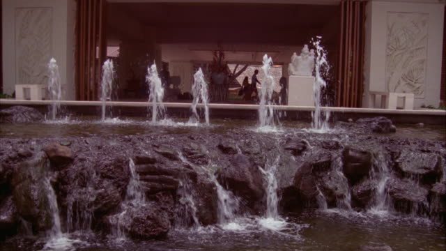 wide angle of fountain with rock formation in front of building. water flows over rocks in small waterfalls. see people and tourists walking in bg building may be museum or government building. - oahu stock videos and b-roll footage