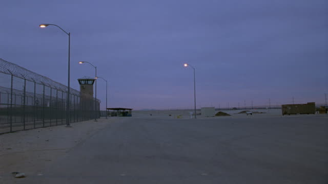 vídeos y material grabado en eventos de stock de wide angle from outside prison gates. see guard tower in background to left. pov from side of road. see traffic driving in different directions outside of prison. dawn. - puerta estructura creada por el hombre