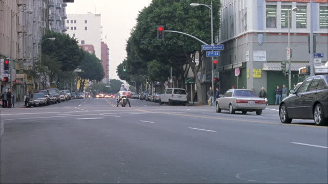 WIDE ANGLE OF BUSY CITY STREET. SEE POLICE MOTORCADE DRIVING FROM BACKGROUND. ONE MOTORCYCLE STOPS AT LIGHT, ONE TURNS, OTHER DRIVES TOWARD AND OUT OF SHOT.