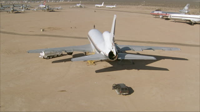 AERIAL OVER LARGE COMMERCIAL AIRLINER IN DESERT AIRPORT. SEE SWAT MEMBER ON TOP OF PLANE.