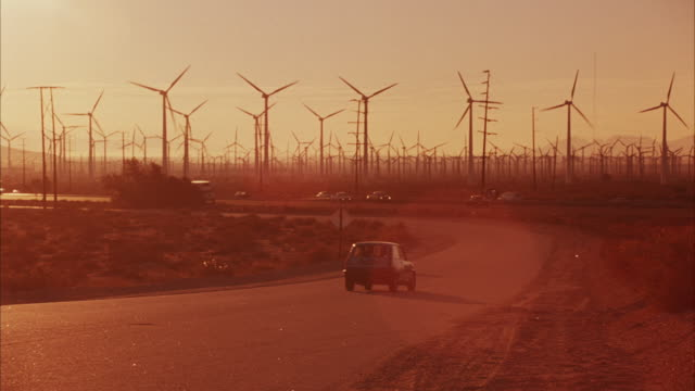 MEDIUM ANGLE GROUP OF WIND TURBINES, ELECTRICITY GENERATORS, SOME REVOLVING. SEE HIGHWAY IN FRONT OF TURBINES, TRAFFIC MOVING IN BOTH LANES. SEE BLUE RENAULT LE CAR DRIVE AWAY FROM POV TOWARDS HIGHWAY. ENERGY, POWER PLANTS.