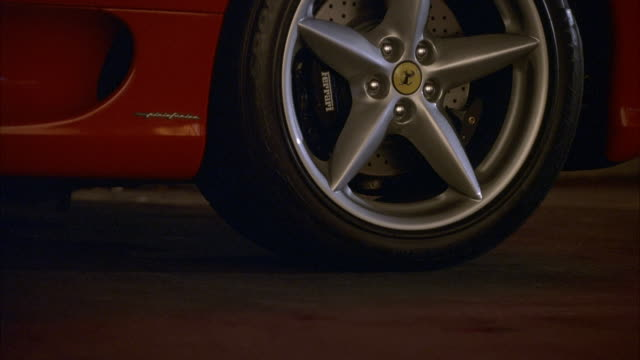 CLOSE ANGLE, REAR TIRE OF RED FERRARI. SEE CAR DRIVE RIGHT TO LEFT, EXIT LEFT, SEE DRIVE AND PLANTS BEYOND.