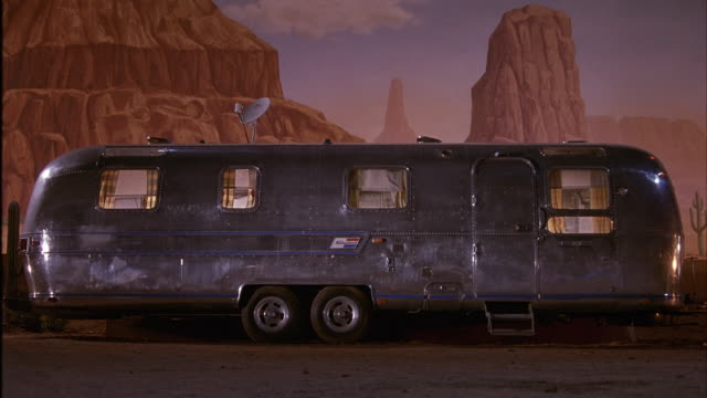 medium angle air stream trailer or rv, satellite on top, painted backdrop of monument valley behind. see gunfire, shots hit trailer and tires. see sparks fly, window panes fall. - see other clips from this shoot 2317 stock-videos und b-roll-filmmaterial