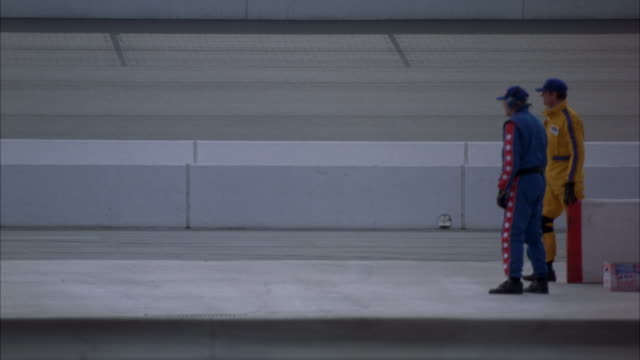 WIDE ANGLE OF MAN IN BLUE AND RED JUMPSUIT CROUCHED TO LEFT NEXT TO WHITE CONCRETE BARRIER AT SIDE OF PAVEMENT AT RIGHT. COULD BE PIT CREW ENTRANCE AT RACE TRACK.