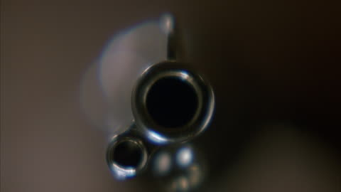 close angle into bore or barrel of metal silver hand gun. see blurred person holding gun in background. see gun held steady as bullet is fired from gun and smoke fills pov. - handgun stock videos & royalty-free footage