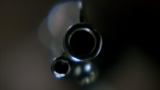 close angle into bore or barrel of metal silver hand gun. see blurred person holding gun in background. see gun held steady and pov flash white as bullet is fired from gun. see smoke fills pov. - handgun stock videos and b-roll footage
