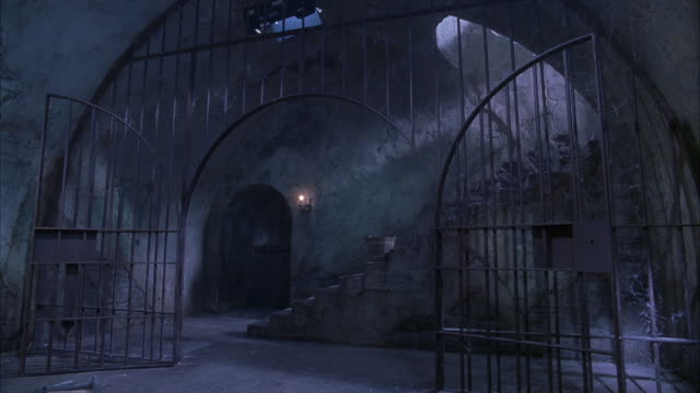 MEDIUM ANGLE OF CONCRETE STAIRCASE BEHIND ARCHED BLACK IRON GATE COVERED IN SPIDER WEBS. COULD BE DUNGEON OR PRISON. SEE DOOR AT BOTTOM LEFT. SEE CANDLES ON WALL AT RIGHT OF DOOR. SEE BLACK-CLAD FIGURE BEGIN TO DESCEND STAIRS.