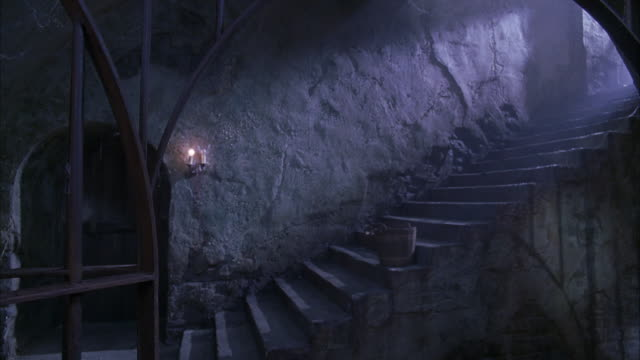 medium angle of concrete staircase behind arched black iron gate. could be dungeon or prison. see wooden door at bottom left. see candles on wall at right of door. see wooden bucket on stairs. see textured wall in background. - steps and staircases stock videos & royalty-free footage