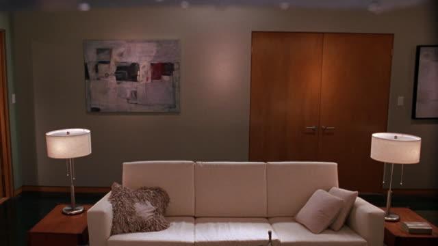medium angle of living room. see white couch set in middle of living room. see two end tables on each side of sofa. - 2000 2010 stil bildbanksvideor och videomaterial från bakom kulisserna