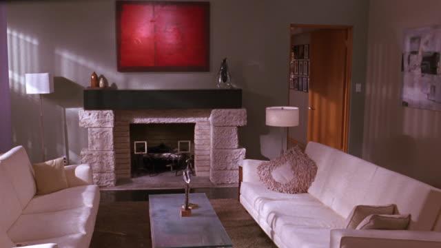 medium angle of contemporary or modern-style living room. see two white sofas set across each other in middle of room. - 2000 2010 stil bildbanksvideor och videomaterial från bakom kulisserna