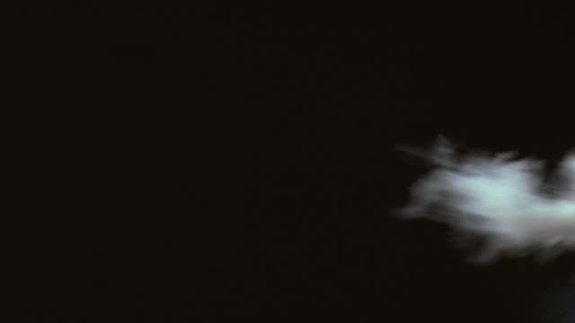 medium angle of wisps of smoke blowing from frame right against black background. - wispy stock videos and b-roll footage