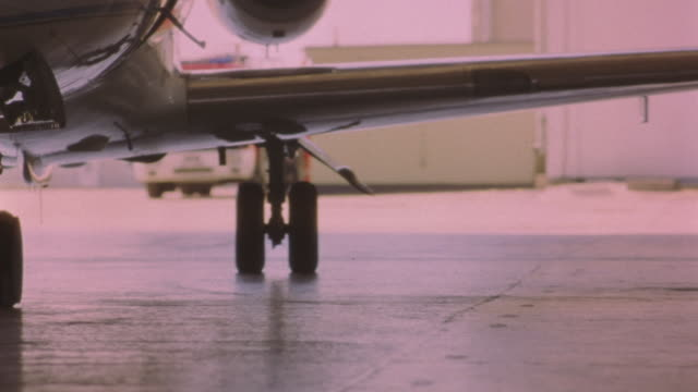 medium angle of private jet entering airport hangar. jet door opens while jet continues to move. 21 fps. plane is hawker siddeley hs 125-700b. - airplane hangar stock videos and b-roll footage