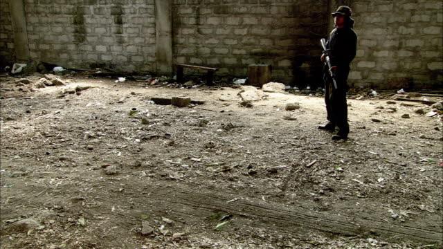 vidéos et rushes de wide angle of gunman or guard standing near cinder block compound wall. large truck arrives. - parpaing