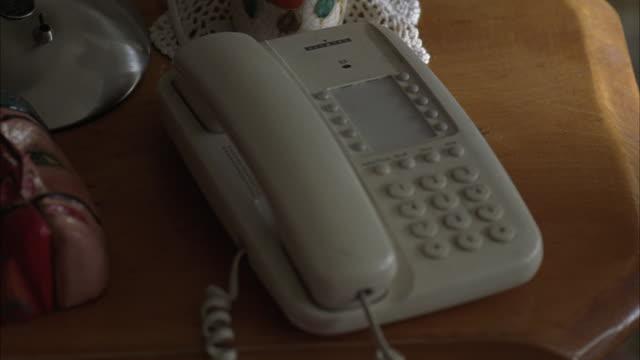 vídeos y material grabado en eventos de stock de hand held, close angle of white home telephone on wooden desk with paper mache mask, other knick-knacks. - papier