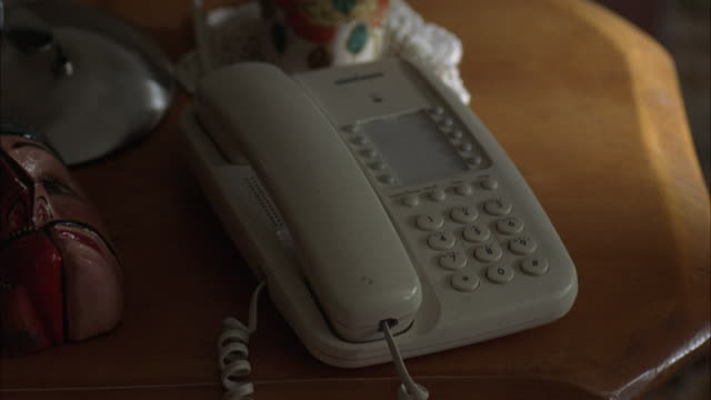 hand held, close angle of white home telephone on wooden desk with paper mache mask, other knick-knacks. - papier 個影片檔及 b 捲影像