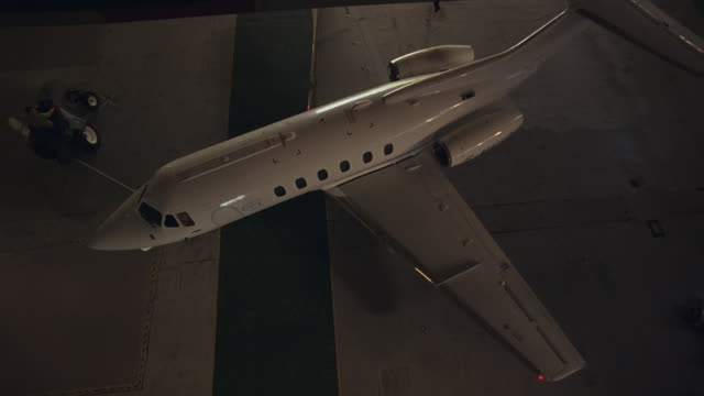 high angle down shows private jet towed by tractor being turned around and pulled out of airplane hangar. plane is hawker siddeley hs 125-700b. - 飛行機格納庫点の映像素材/bロール