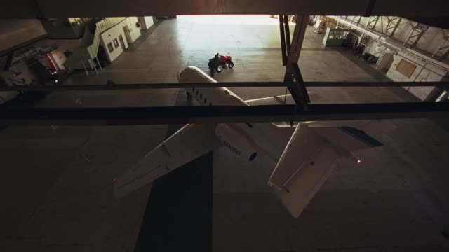 high angle down shows private jet towed by tractor being turned around and parked in airplane hangar. plane is hawker siddeley hs 125-700b. - 飛行機格納庫点の映像素材/bロール