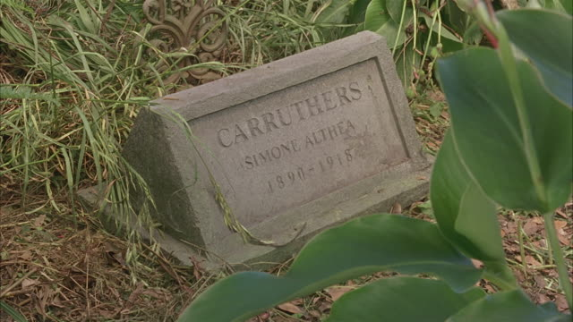 MEDIUM ANGLE OF HEADSTONE OR GRAVESTONE, MARKING THE GRAVE OF SIMONE ATHEA CARRUTHERS, 1890 - 1918.  SOME OVERGROWN PLANTS, GRASS.