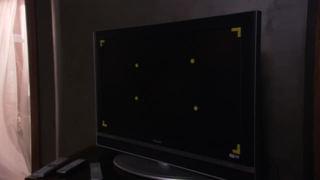MEDIUM ANGLE OF BLACK FLAT SCREEN TELEVISION. SEE YELLOW GRID STICKERS ON TELEVISION SCREEN. SEE NO IMAGE ON TELEVISION. CAMERA IS TILTED LEFT.