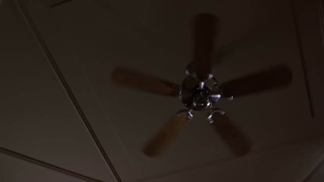 up angle establish of ceiling fan. fan moves at moderate speed then turns faster. - ceiling fan stock videos & royalty-free footage