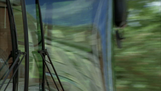pan left to right as a bus drives past a park.  the bus driver can be seen through the window. - bus driver stock videos & royalty-free footage