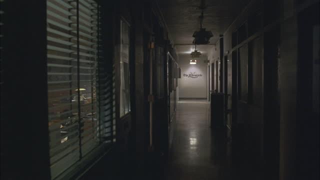 medium angle of old fashioned office hallway with window blinds on windows. - corridoio caratteristica di una costruzione video stock e b–roll