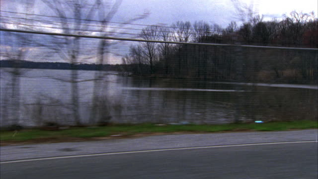 WIDE ANGLE OF ROADSIDE, FENCE, AND LAKE FROM MOVING VEHICLE. LAKE APPEARS BEHIND CHAIN LINK FENCE WITH BARBED WIRE ON TOP.