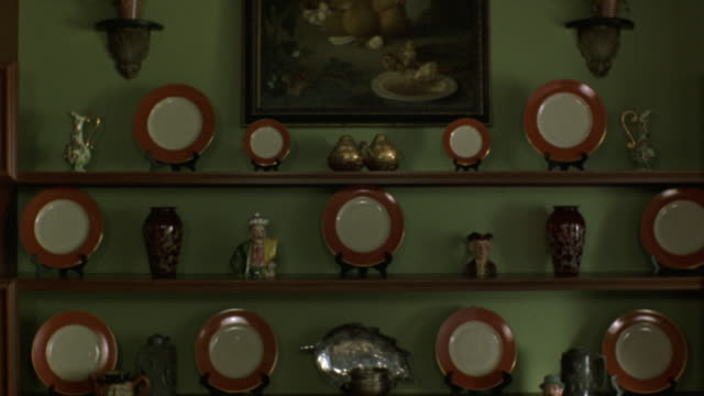 vídeos y material grabado en eventos de stock de medium angle of wooden shelves mounted on wall. see vases and fine china displayed on shelf. see painting in background. - jarra