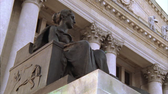 UP ANGLE OF STATUE AND UPPER FACADE OF COURTHOUSE, CITY HALL, OR SIMILAR BUILDING.