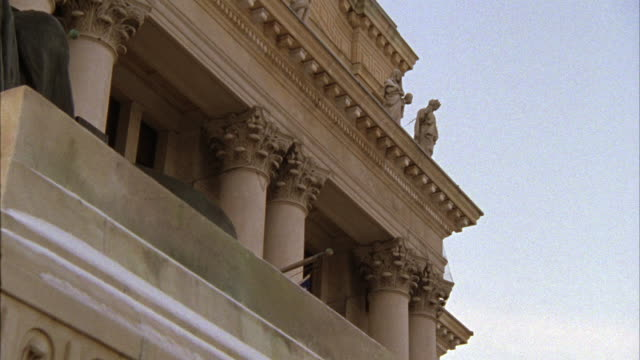 PAN RIGHT TO LEFT, UP ANGLE OF COURTHOUSE OR CITY HALL FACADE AND STATE OF LADY JUSTICE. CAMERA SHOWS UPPER CORNER OF STONE ROOF, PILLARS AND PANS TO STATUE. ARCHITECTURE.