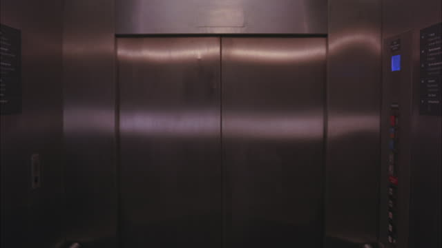 vidéos et rushes de medium angle of elevator interior in modern office building, skyscraper or hospital. doors, buttons seen. - ascenseur