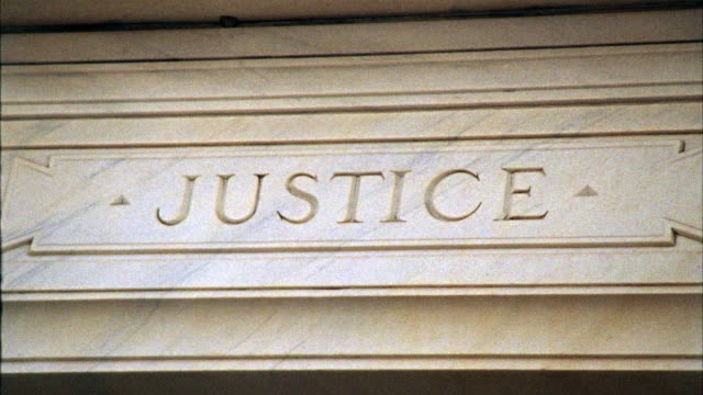 "close angle of stone engraving that reads ""justice"" on exterior of courthouse. - law stock videos & royalty-free footage"